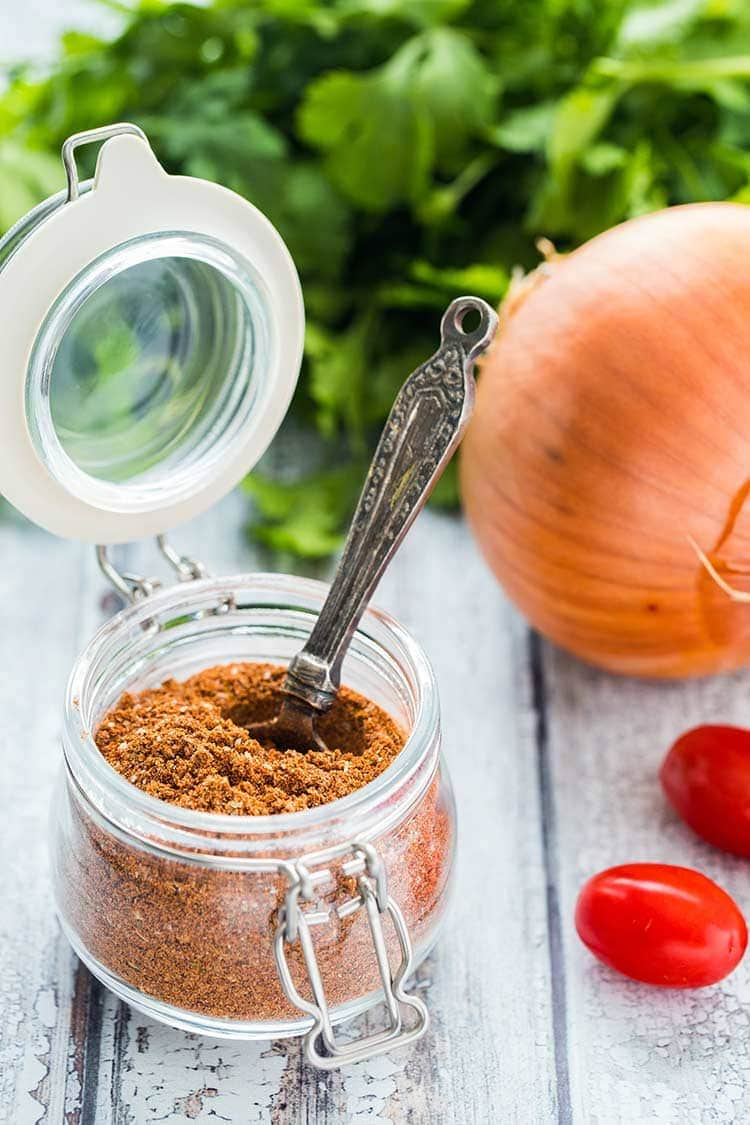 Make Your Own Taco Seasoning in a glass jar with spoon on wooden table with ingredients off to the side