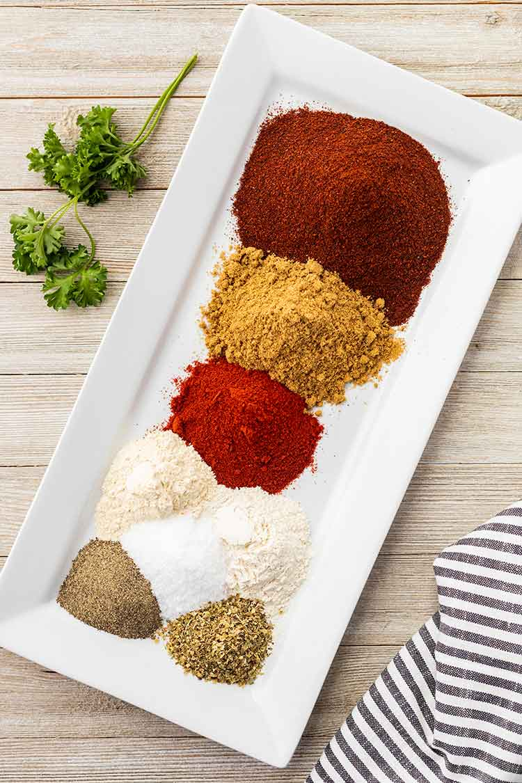 Overhead view of the various spices that are used to make Taco Seasoning Mix in piles on a small rectangular white plate