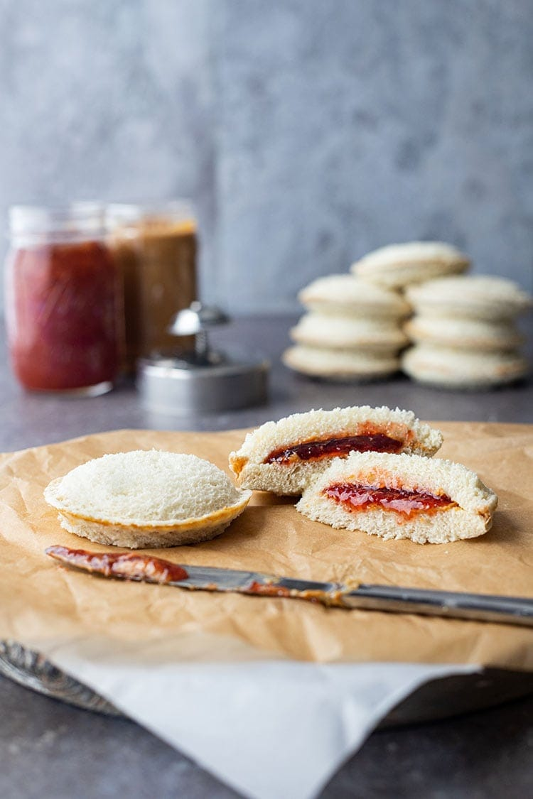 Homemade uncrustables sandwiches sitting on parchment paper on the counter, with ingredients and additional sandwiches in background.