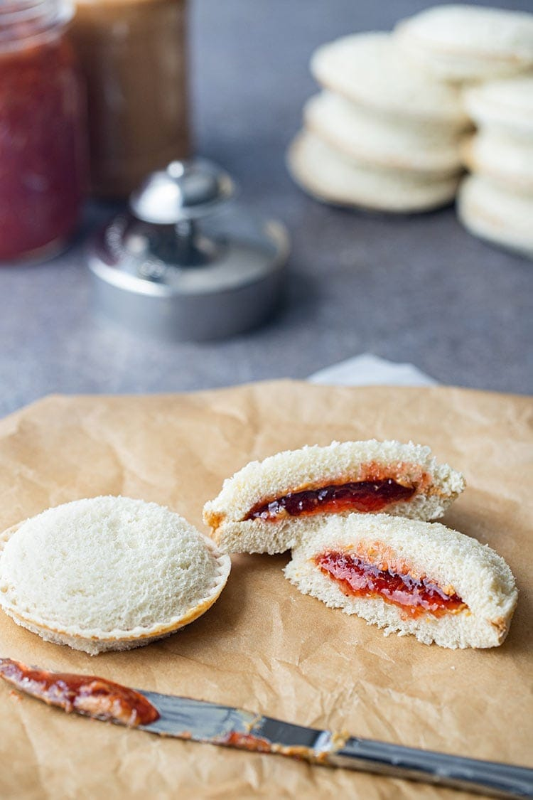 Homemade uncrustables sandwiches on a counter, with one cut open to show the peanut butter and jam filling, with additional sandwiches in background.