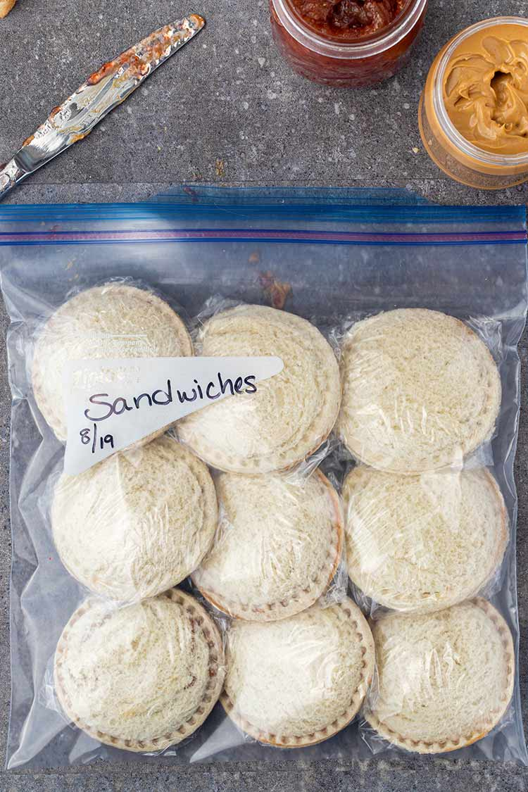 A gallon ziptop freezer bag filled with premade homemade uncrustables sandwiches to be placed in the freezer.