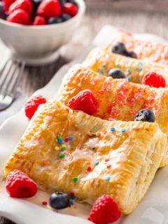 Four baked breakfast pastries layered on a white plate, garnished with fresh fruit, icing, and sprinkles.