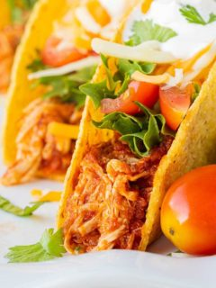 A close up of three tacos made with Instant Pot Salsa Chicken, lettuce, tomatoes, cheese, sour cream, and garnished with cilantro, staggered on a white plate.