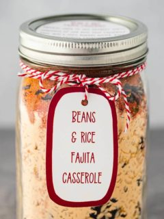 Mason jar, on gray background, filled with the dry ingredients used to make Bean & Rice Fajita Casserole, sealed and a printed label tied to the rim of the jar.