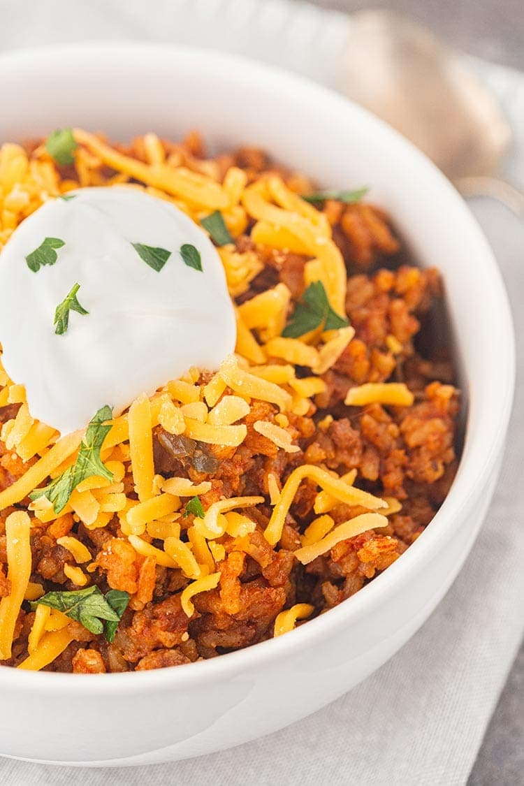 Close up shot of Beef Taco Rice Meal in a Jar in a white bowl, topped with shredded cheese and sour cream.