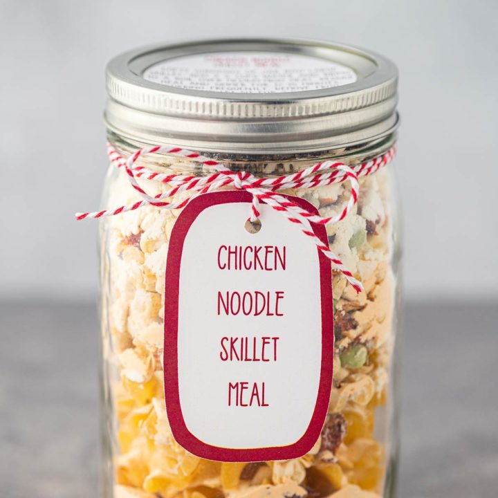 Quart mason jar, on gray background, filled with the dry ingredients used to make Chicken Noodle Skillet Meal, with a printed label tied to the outside of the jar.