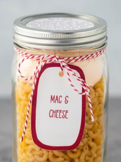 A quart mason jar, on a gray background, filled with the dry ingredients needed to make this Mac & Cheese meal in a jar, with a printed label tied to the outside of the jar.