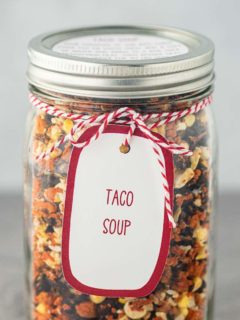 A quart mason jar, on a gray background, filled with the dry ingredients needed to make Taco Soup, with a printed label tied to the outside of the jar.