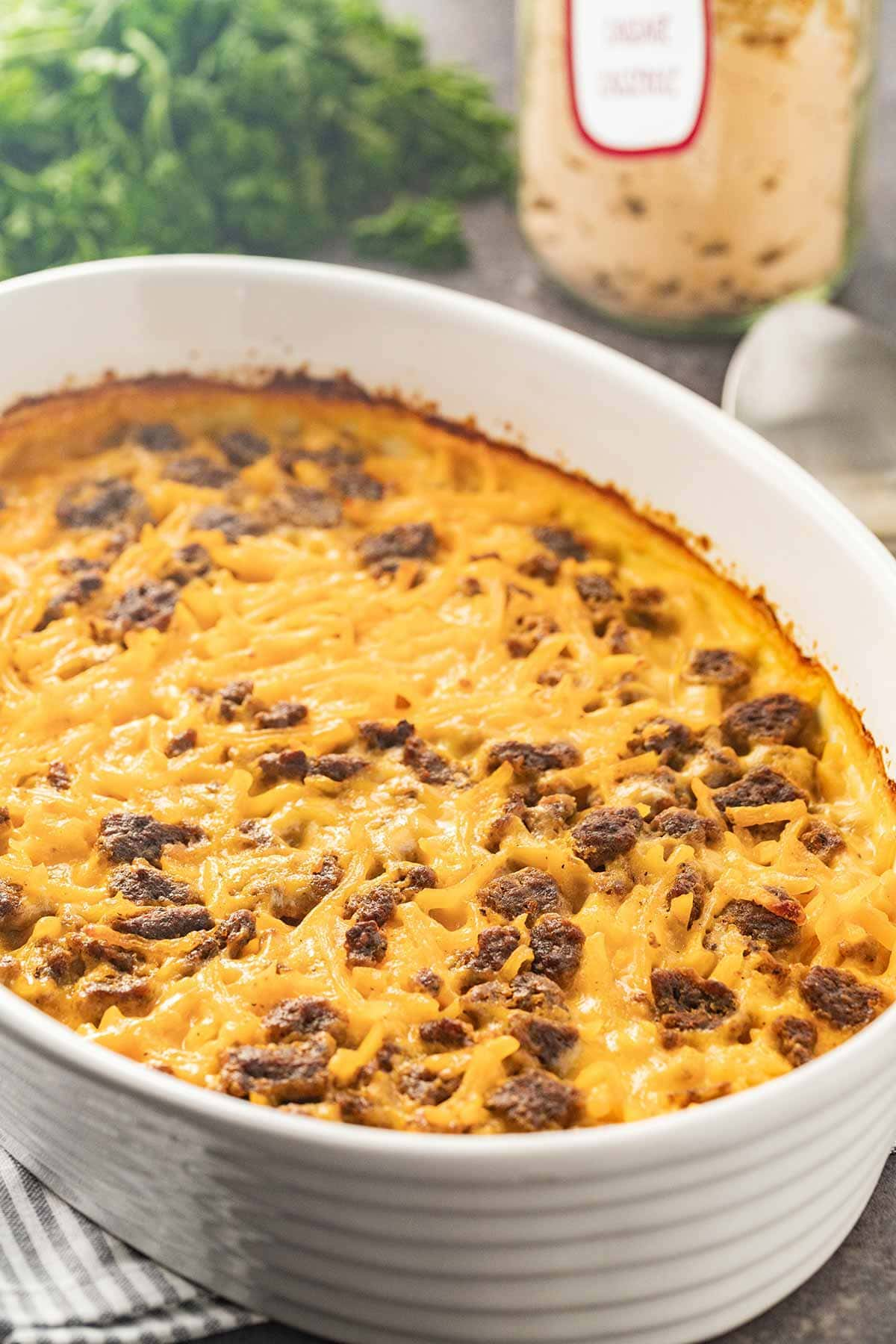 White oval dish showing baked Potato Cheese Sausage Casserole for an easy meal.