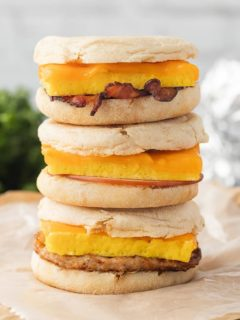 A stack of three Freezer Breakfast Sandwiches on parchment paper, showing the various layers and meat options.