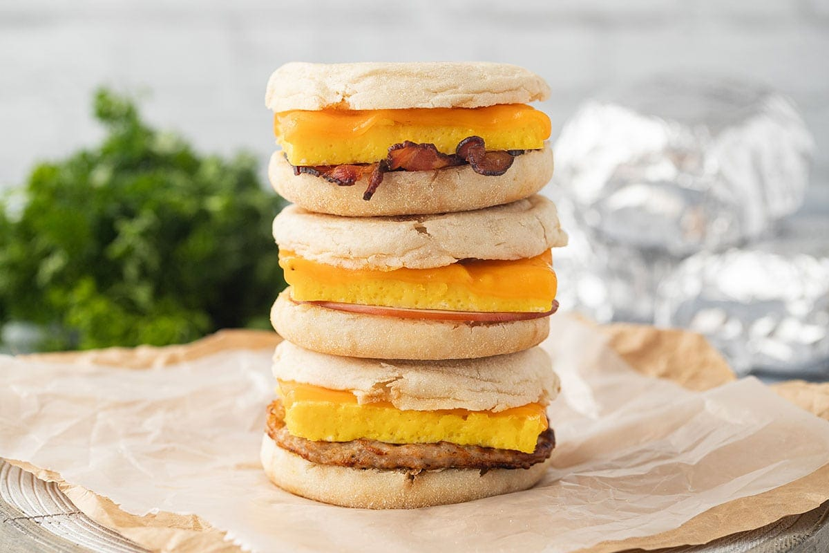 A wide shot showing three stacked Freezer Breakfast Sandwiches with parsley and other wrapped sandwiches in the background.