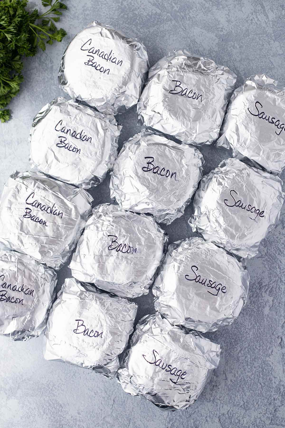 Overhead shot showing a dozen wrapped sandwiches that have been labeled according to the type of meat used.