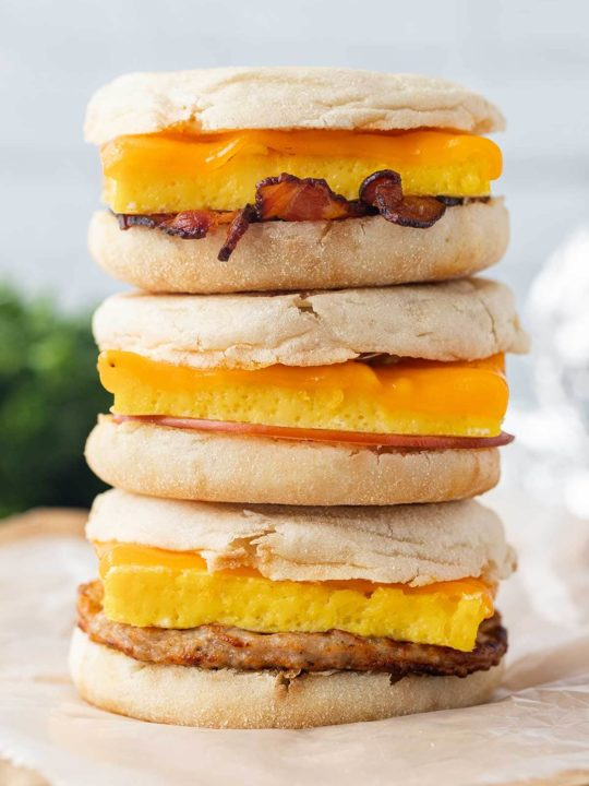 A stack of three Freezer Breakfast Sandwiches, sitting on top of sheets of parchment paper.