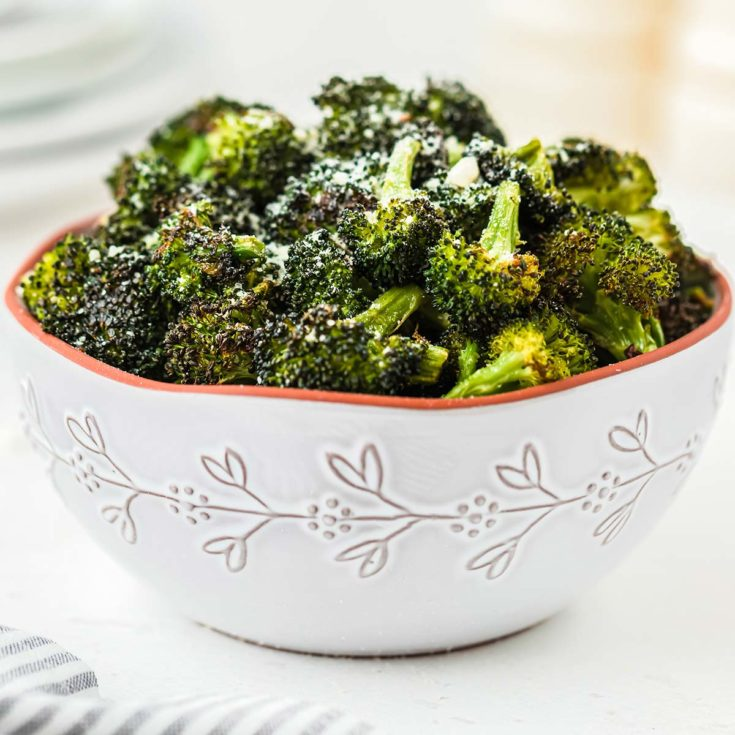 A bowl of roasted broccoli, garnished with grated Parmesan cheese.