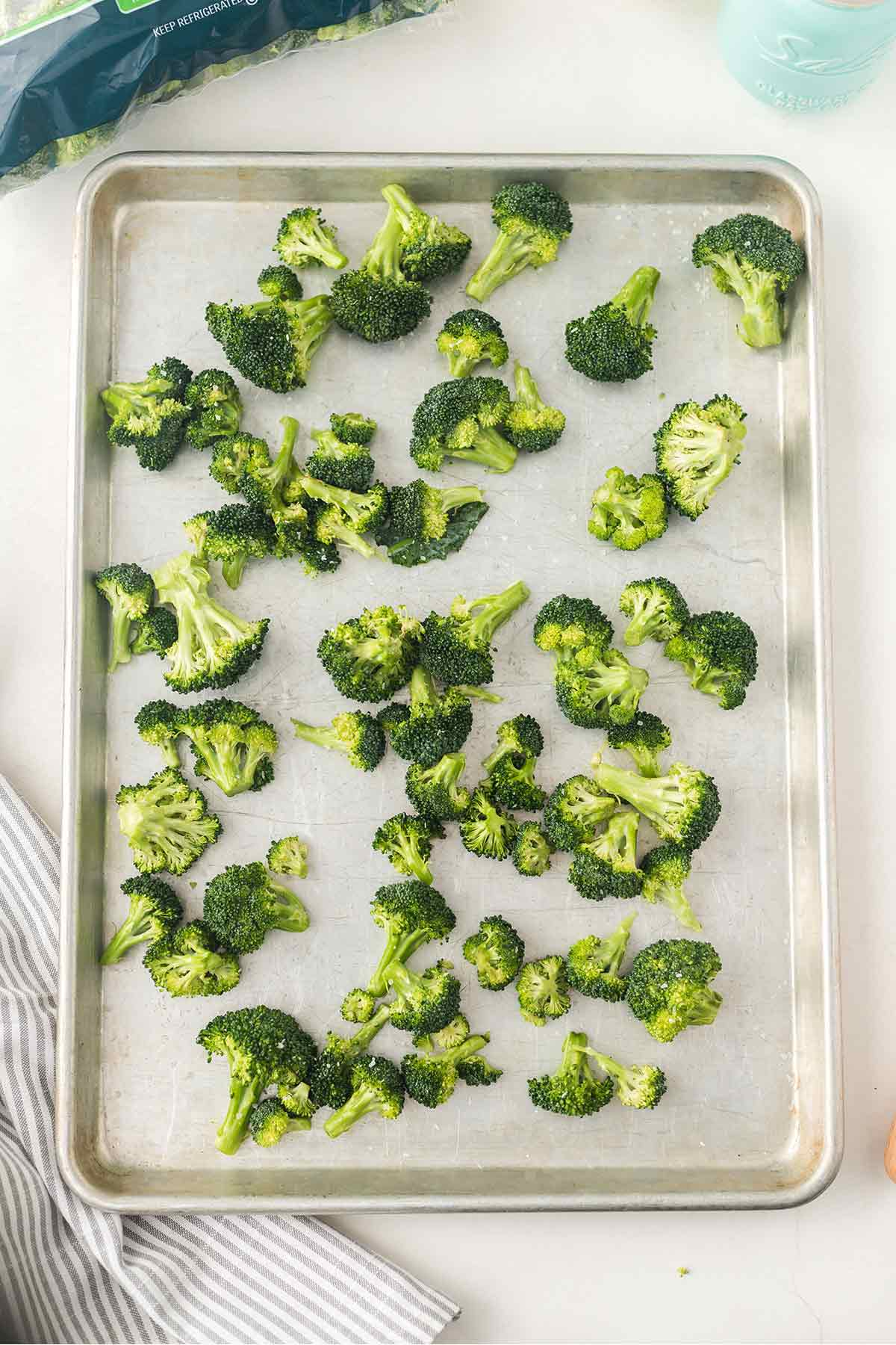 Overhead shot of broccoli florets on baking sheet ready to go into the oven for roasting.