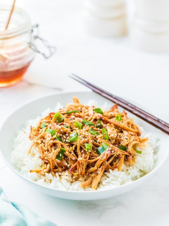 Plate of Honey Sesame Chicken over bed of rice, with chopsticks and honey jar in background.