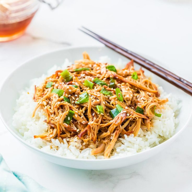 Honey Sesame Chicken cooked and served on a bed of white rice, garnished with toasted sesame seeds and sliced green onions.
