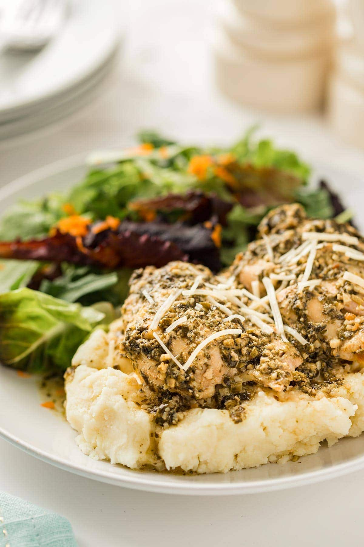 Dinner plate with Pesto Ranch Chicken on top of mashed potatoes.