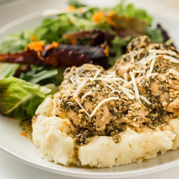 Pesto Ranch Chicken on a bed of mashed potatoes, garnished with shredded Parmesan cheese.